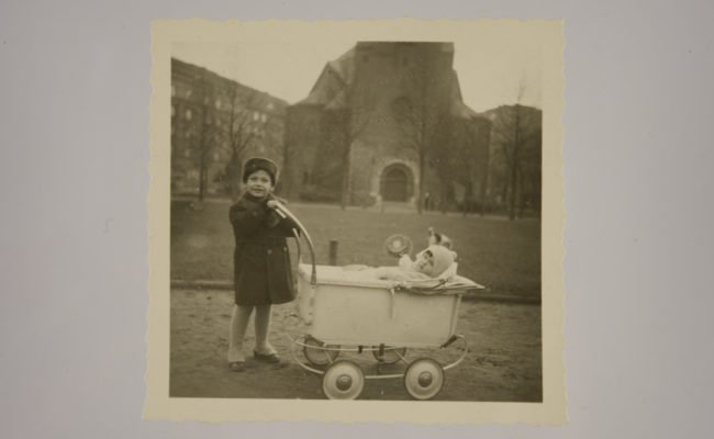 Young boy next to old style pram with a small infant inside
