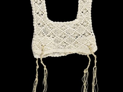 White crocheted vest with tassels at the bottom.