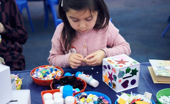 A young girl sitting at a table with blue cloth, glue, and red pots of stickers and gems for a craft activity