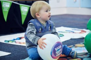 An infant boy sitting on a carpeted floor and rug holding a white balloon with multicoloured logo on that reads Inter Faith Week