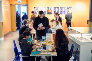 An adult male stands at a table of children. On the table is lots of card, glue and other craft activities