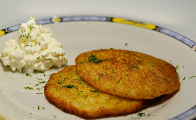 Two small potato latkes (pancakes) with herb garnish on a plate with a dollop of sour cream