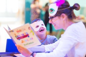 Adult female reads to small child who sis laughing. Both are wearing masks