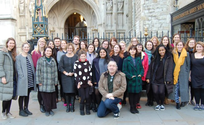 A large group of mixed adults standing outside of Westminster Abbey gates