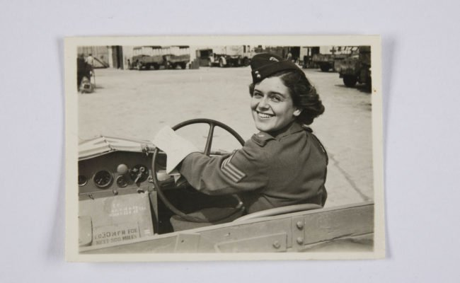 a woman in war time uniform driving an open top car looks back over her shoulder with a smile