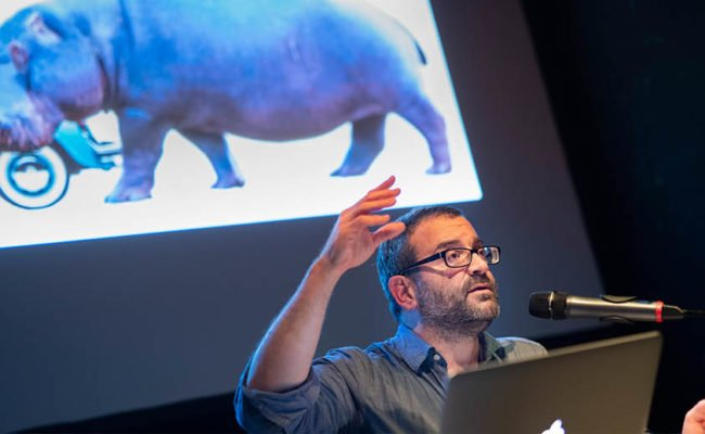 Man on stage talking into mic with laptop. Behind a screen projects an image of a blue hippo.