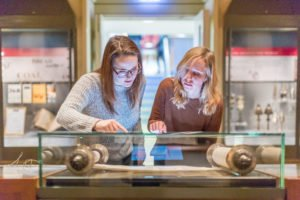 Two adults looking at a Torah scroll in the Judaica gallery