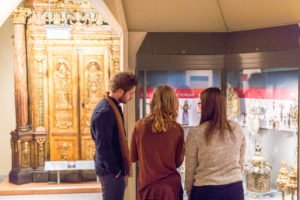A man and two women looking at gold objects in a glass case