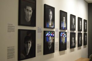 A series of black and white portraits lined up in two rows on a white wall