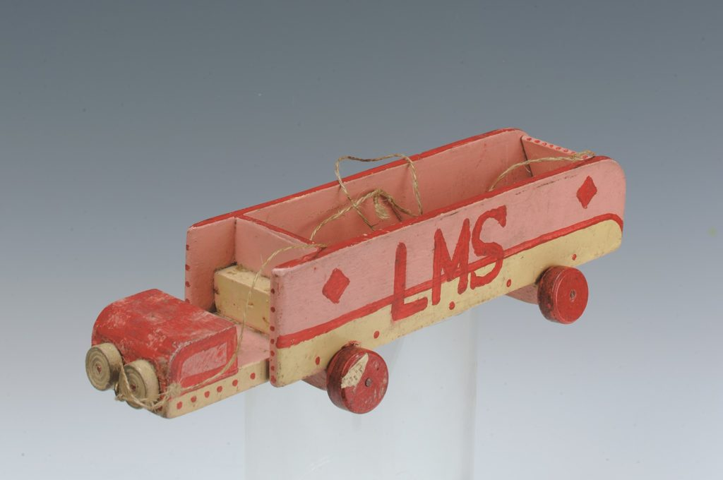 "A red and brown wooden truck with the letters ""LMS"" painted on the side"