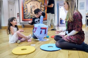 Two children and a woman sat on the floor playing with toys