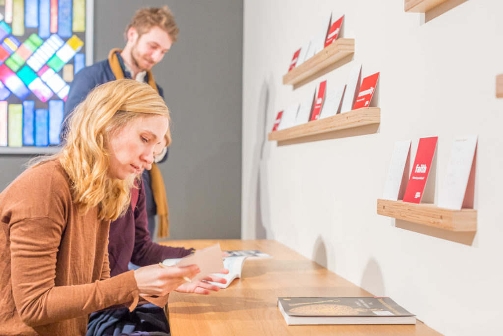 A blonde woman and a dark haired man looking at books on a table