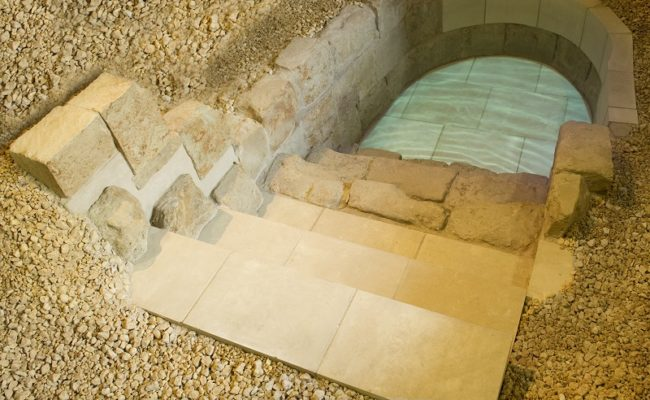 A stone pool surrounded by smaller beige stones