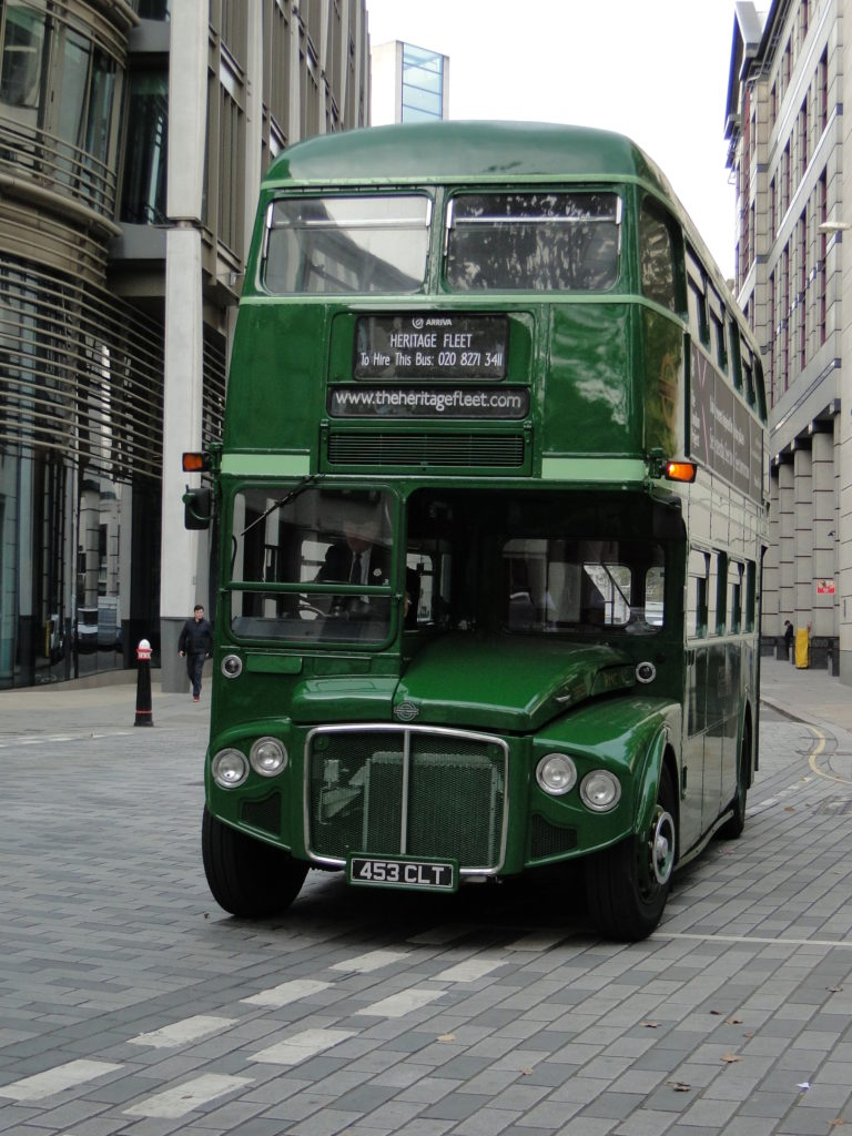 A double decker green bus on a road