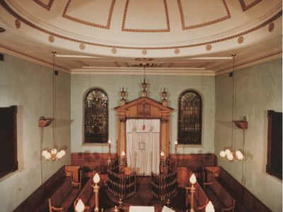 Photograph of synagogue with pale walls, high ceilings, wooden benches and a large white ark.