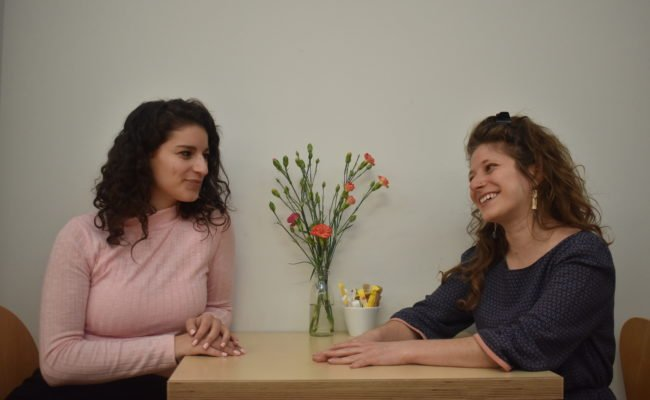 Two woman sat at a table talking