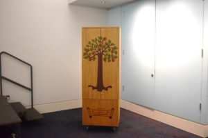 A wooden case with a painted front in a blue room