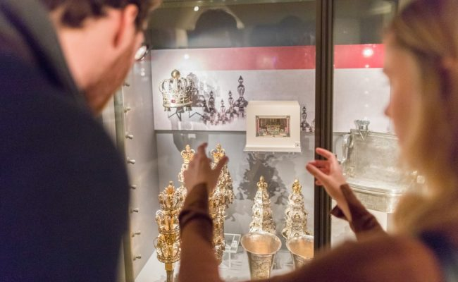 A man and a woman looking at silver objects in a glass case