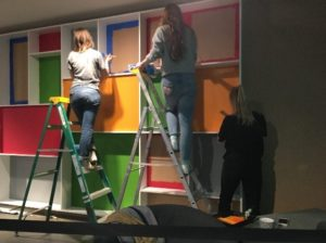 A group of people climbing up ladders in front of a colourful wall