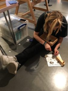 A woman assembling a wooden item with a screwdriver