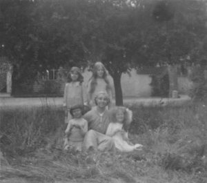 B&W photo of a group of people sat in grass with trees behind them