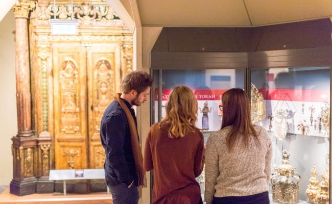 Three people stood in a room with a glass case looking at items in it