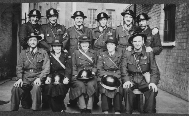 B&W photo of a group of men in uniforms sat together