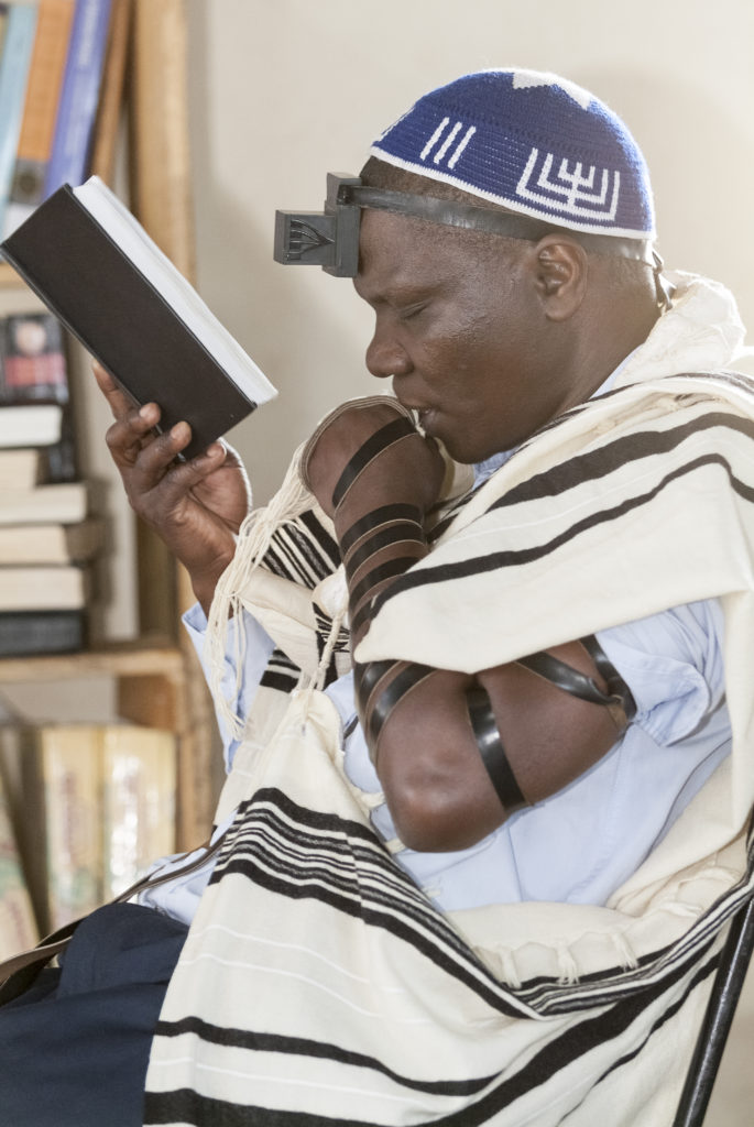 A man wearing a head covering reading a book