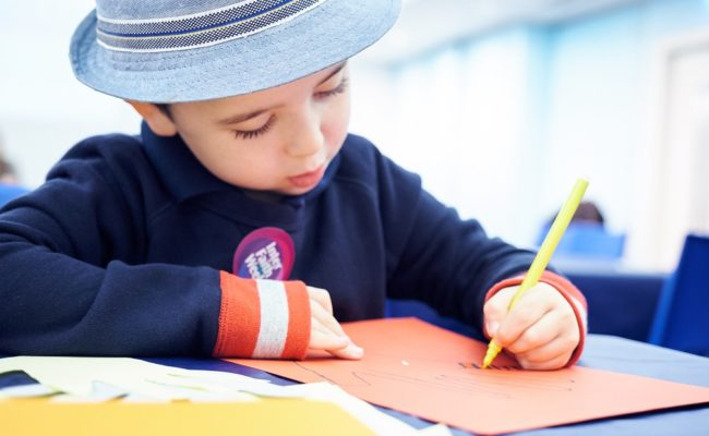 A boy in a hat drawing
