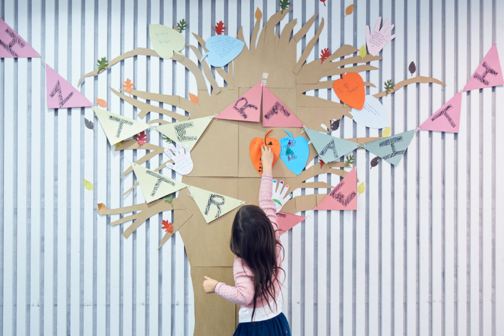 A girl sticking paper on the wall