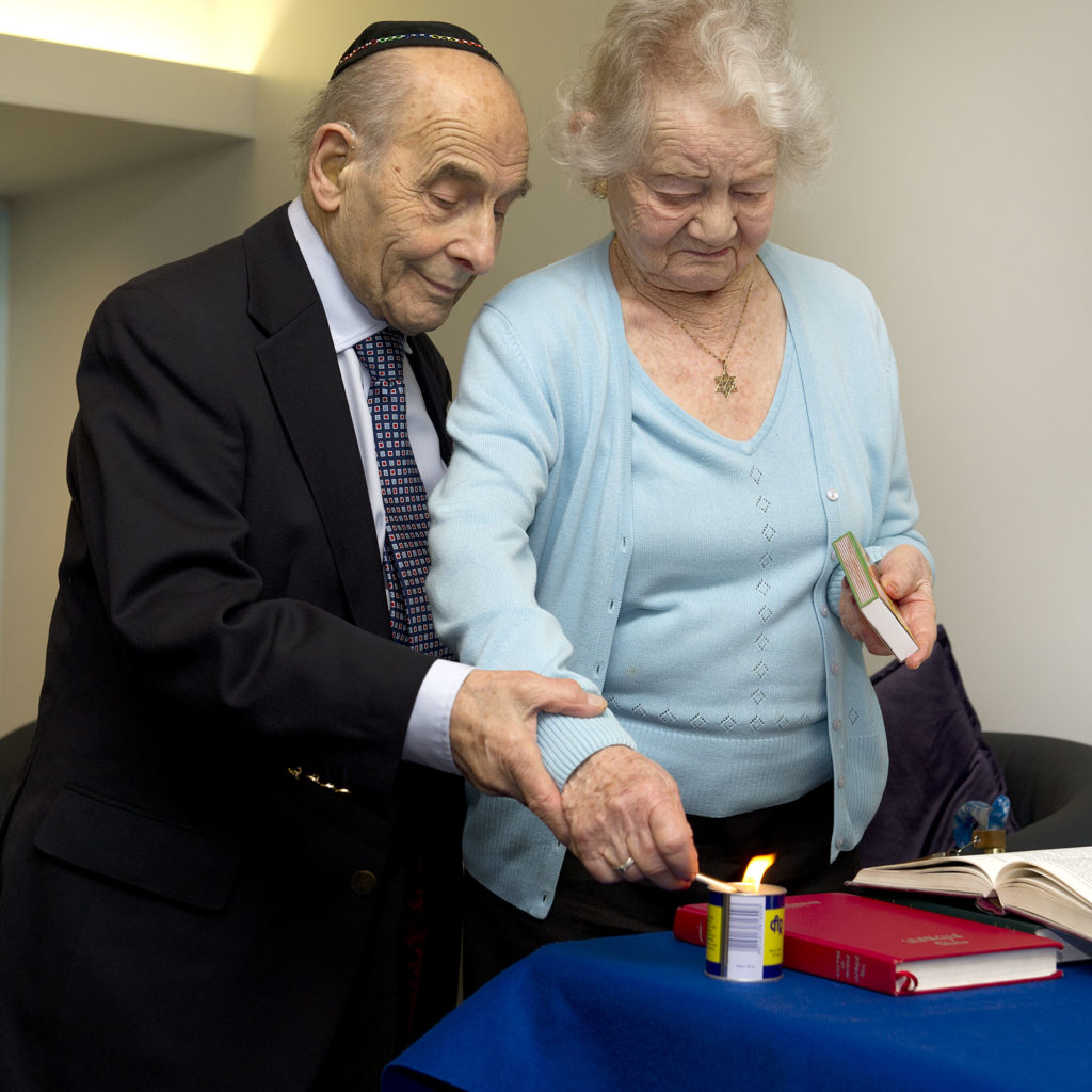 A man and a woman lighting a candle