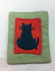 A green and red cloth with a black cat on it