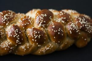A plaited loaf of bread covered in seeds