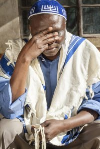 Man praying, wearing prayer shawl and skull cap.