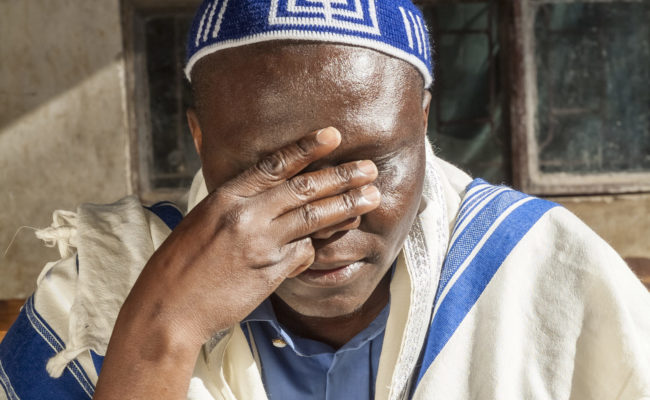 Man praying, wearing prayer shawl and skull cap.